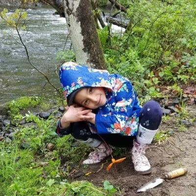 A little girl plants a tree along New York trout stream