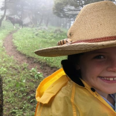 A little girl wearing a cowboy hat smiles amid a Montana rain storm.