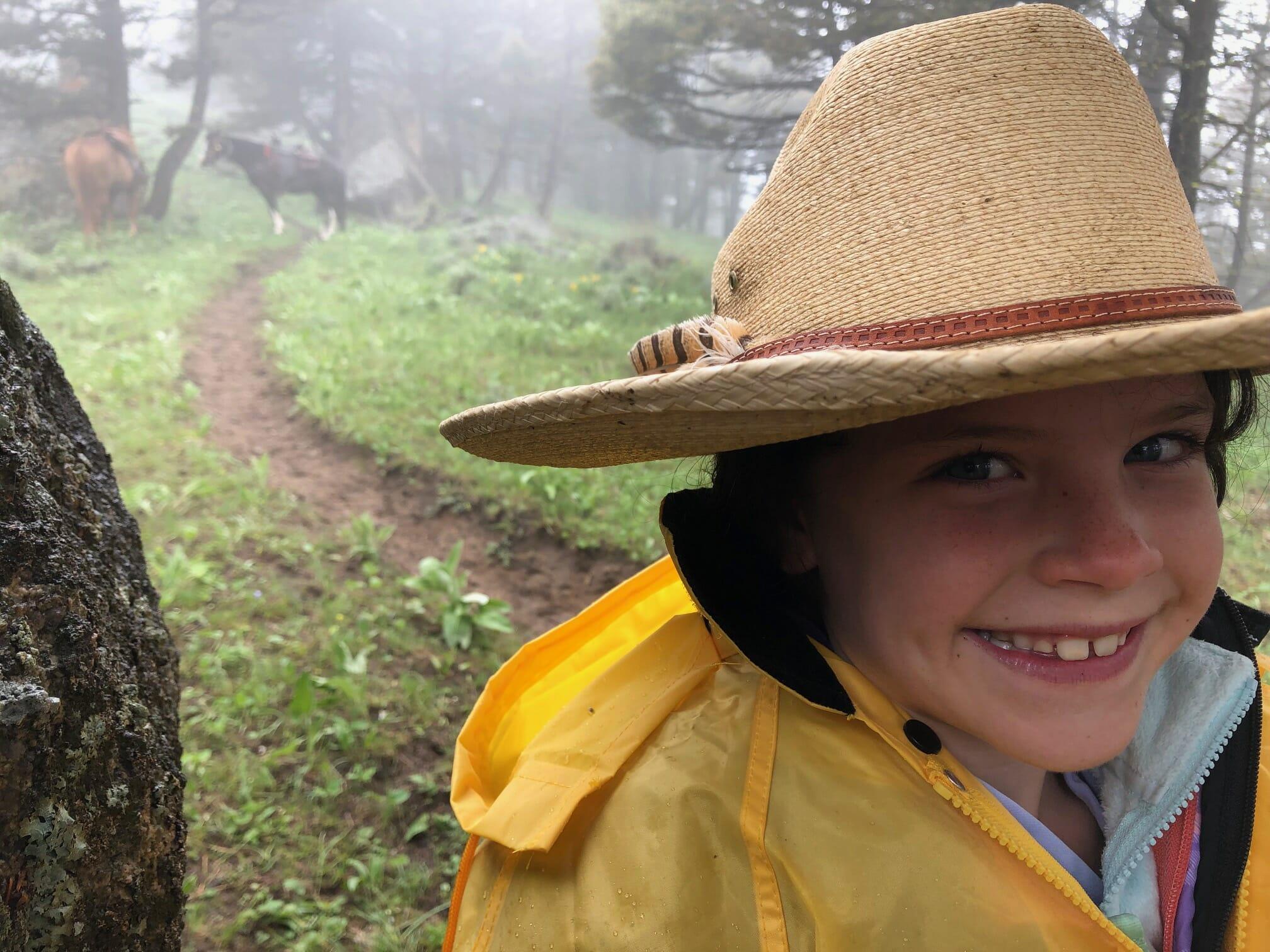 A little girl wearing a cowboy hat smiles amid a Montana rain storm.