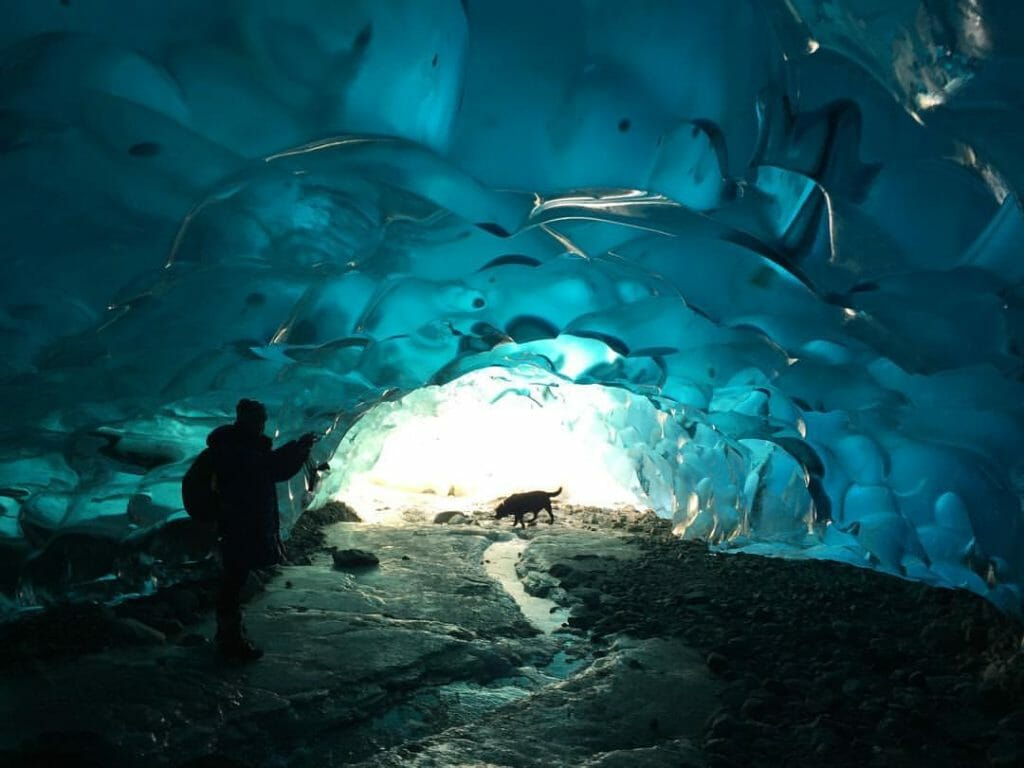 A woman and her dog explore an ice cave near Juneau, Alaska.
