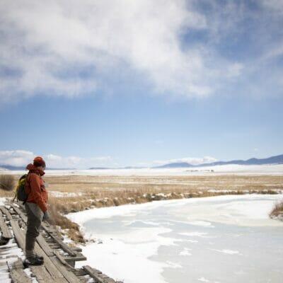 An angler stands over a frozen creek.