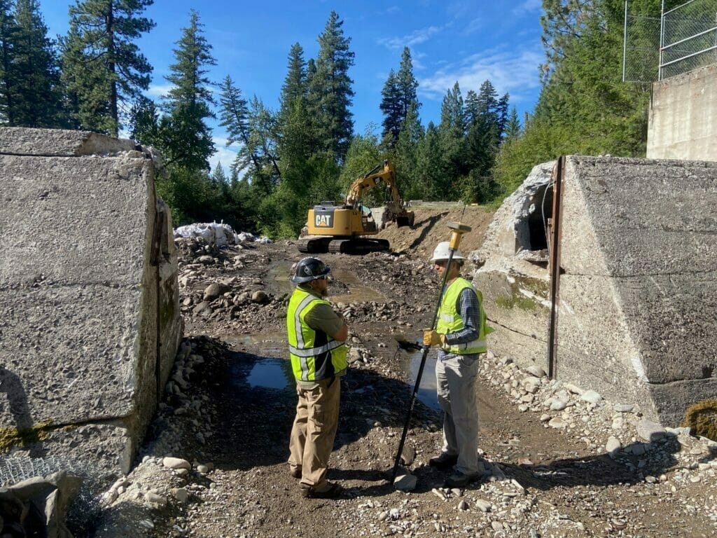 Two construction workers help remove a dam in Montana.