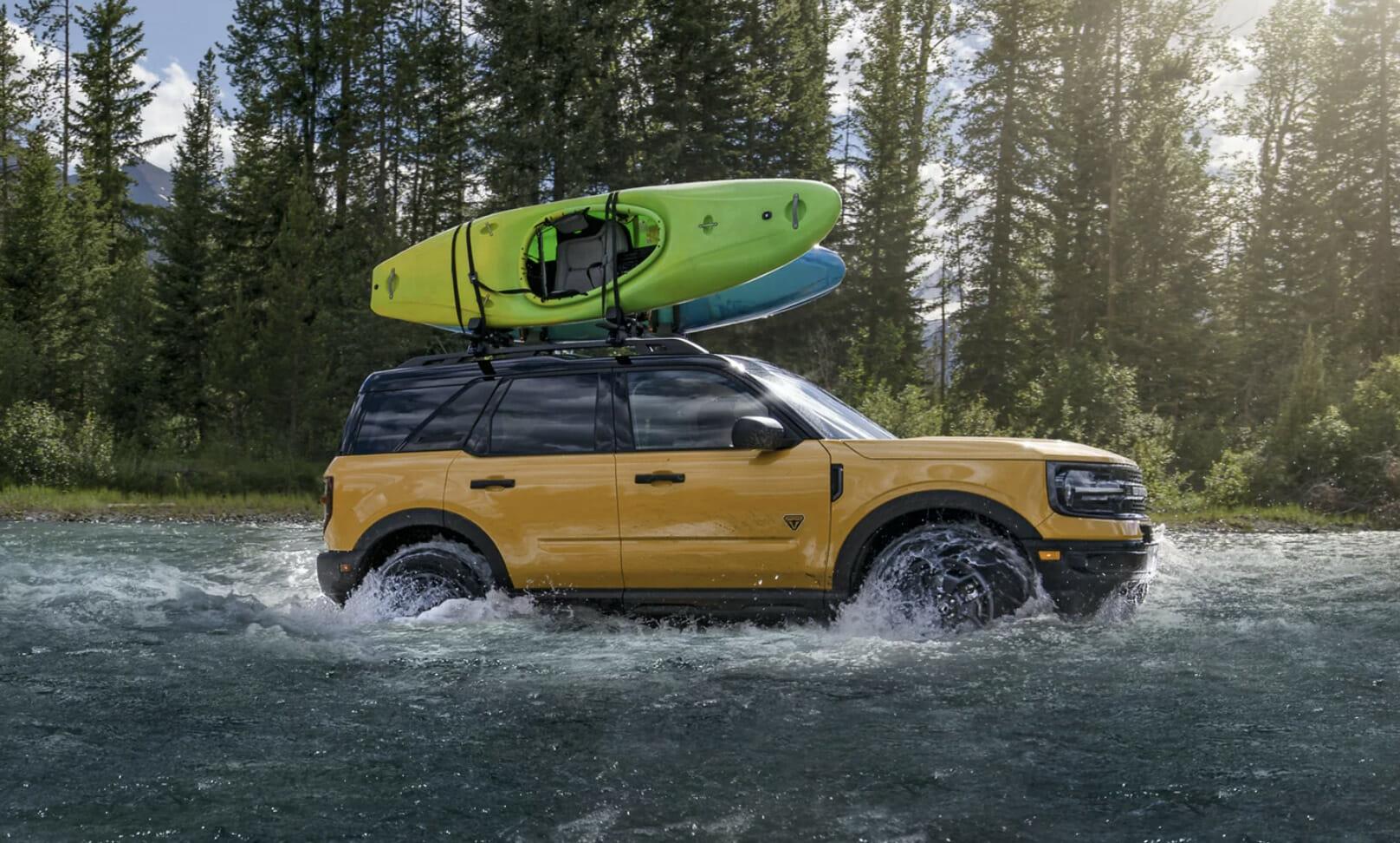 A Ford Bronco drives through a river.